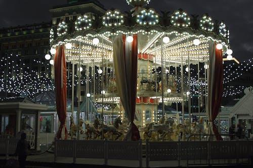 Illuminated merry go round in amusement park at night