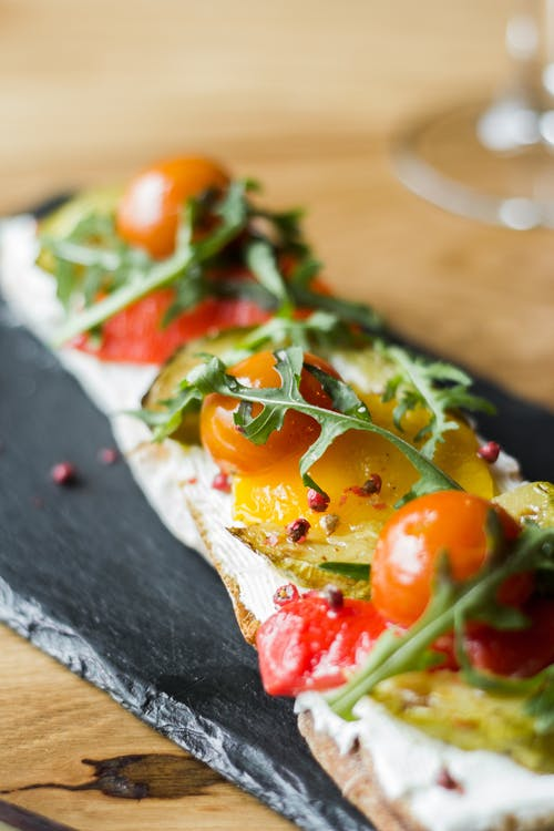 Pizza With Tomato and Green Leaves on Brown Wooden Table