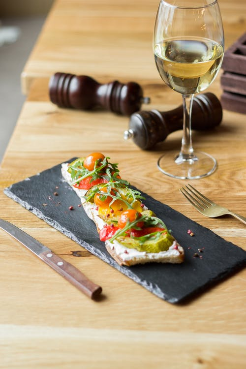Sliced Pizza on Brown Wooden Chopping Board Beside Clear Wine Glass