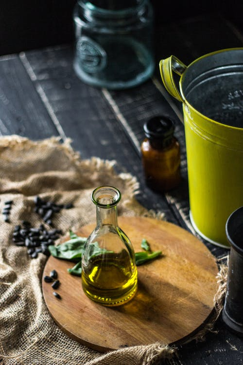 Clear Glass Bottle Beside Green Ceramic Mug on Brown Wooden Table