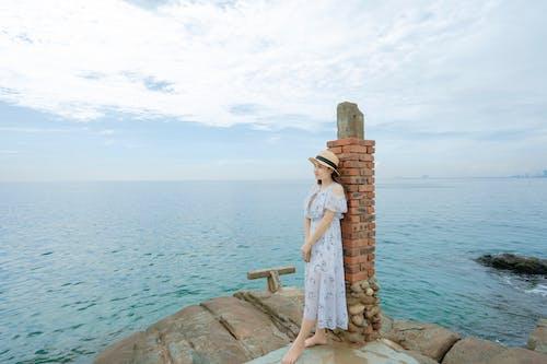 Young woman enjoying seascape on rocky coast