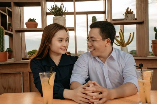 Smiling Asian couple in elegant clothes sitting at table with drinks in cafeteria and holding hands while looking at each other in daytime with shelves with potted plants on background