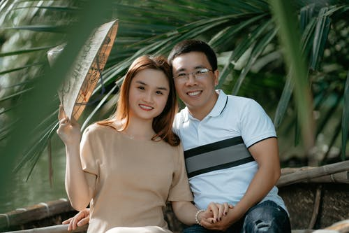 Smiling ethnic couple on boat in water near plants