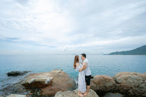 Side view full body of barefoot couple in summer clothes cuddling on big boulders on beach near sea in summer day under cloudy sky while looking at each other