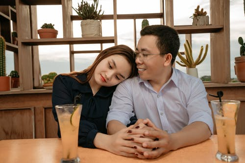 Asian couple having date in cafeteria with drinks