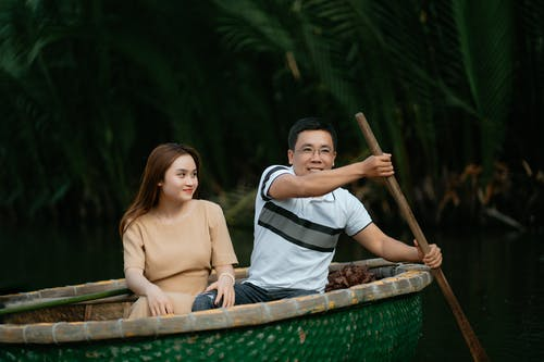 Asian couple in casual outfits sitting on boat in water and man using paddle for floating near green plants in daylight