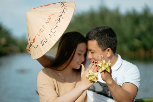 Unrecognizable happy Asian couple in casual outfits with coolie hat sitting in boat on river with gift bow on fingers on honeymoon in summer sunny day