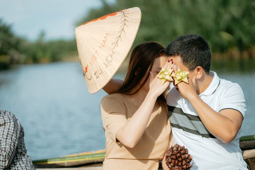 Anonymous couple in casual outfits and coolie hat with gift bow on fingers and cone sitting in boat while floating on water in honeymoon in summer sunny day