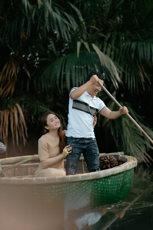 Positive Asian couple in casual outfits rowing with paddle while floating in boat against green plants in daylight