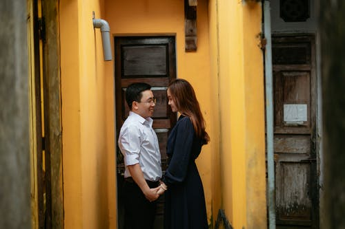 Side view of young well dressed glad couple interacting and looking at each other between aged building walls