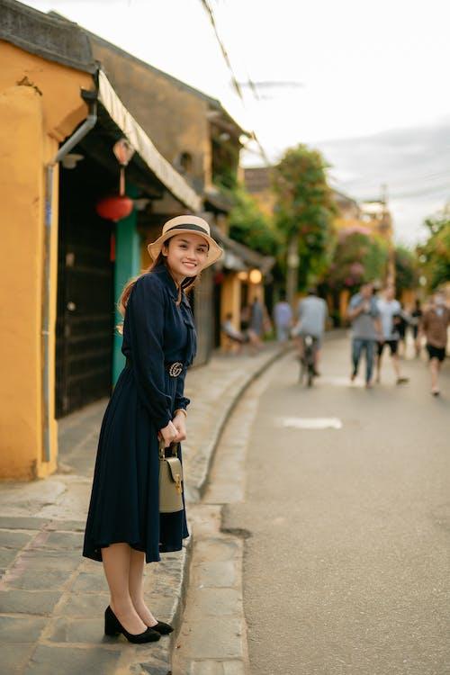 Smiling elegant Asian tourist on city street