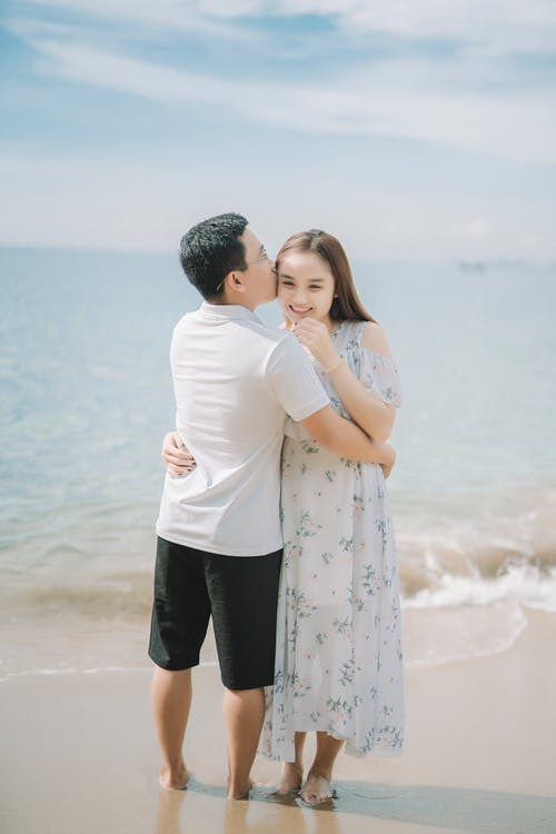 Ethnic man kissing and embracing charming girlfriend while standing on sandy ocean coast during summer trip