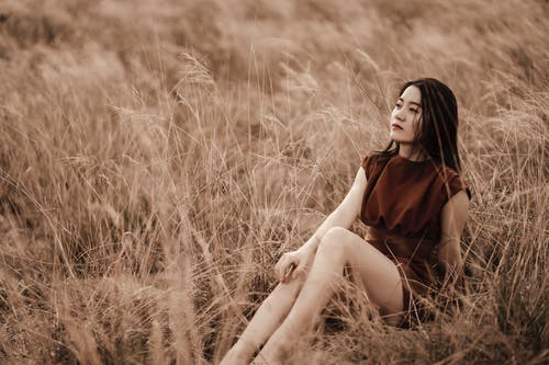 Young dreamy ethnic female in stylish apparel sitting on faded grass and looking up in daylight