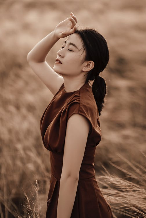 Side view of young dreamy Asian female in elegant clothes with closed eyes on meadow on blurred background