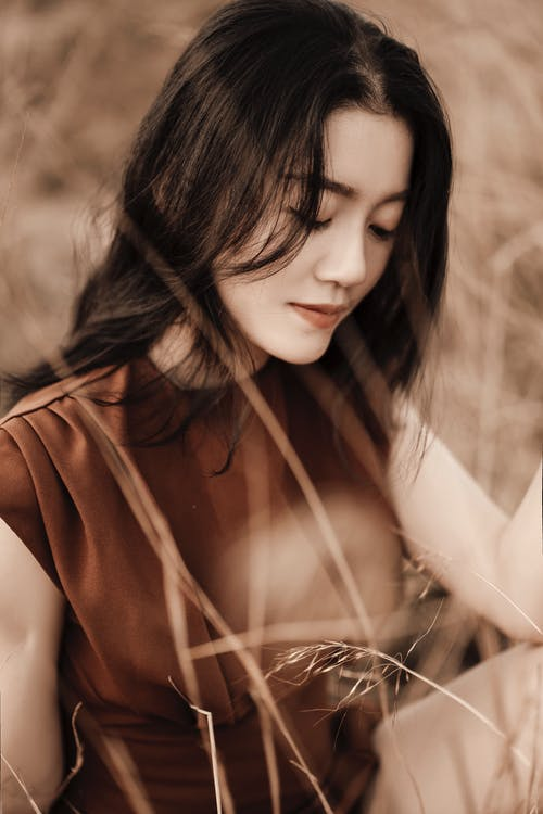 Dreamy Asian woman with closed eyes in field