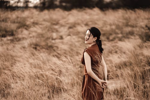 Side view of sincere ethnic female in stylish clothes with hands behind back looking away among faded grass