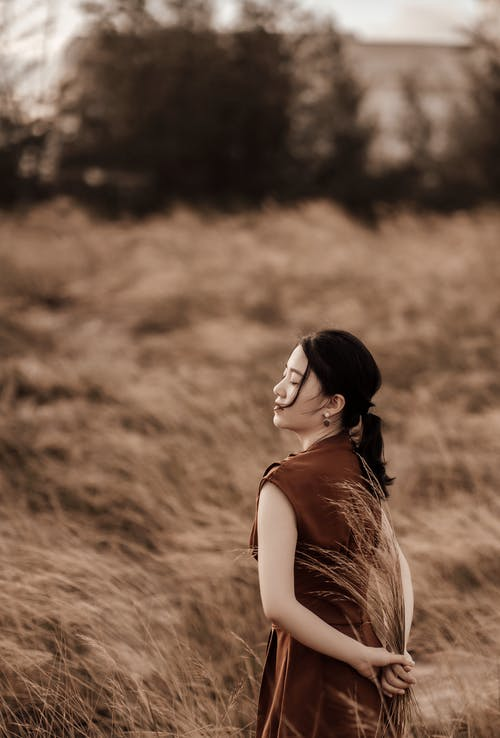 Dreamy ethnic woman in stylish outfit in countryside field