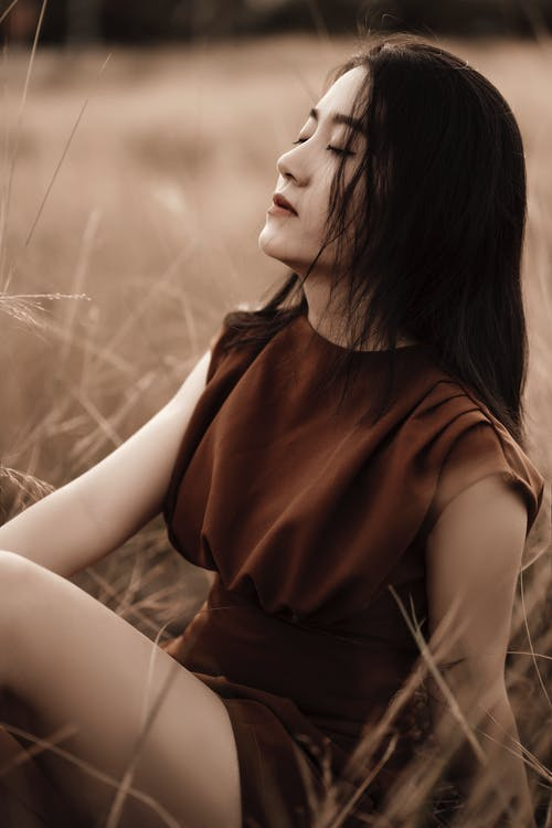 Side view of millennial ethnic female with makeup in brown apparel sitting in countryside field in daytime