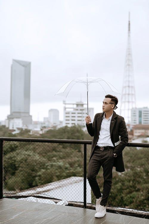 Stylish ethnic man with umbrella against modern city buildings