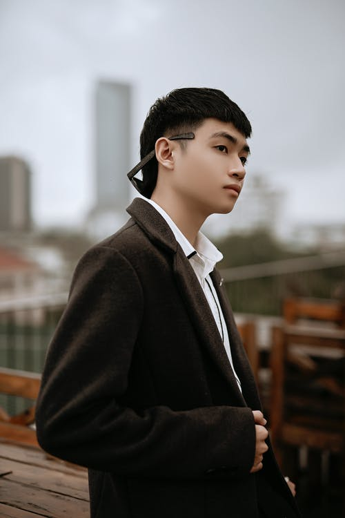Side view of young pensive well dressed ethnic male in coat looking away in urban cafe
