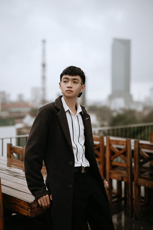 Young wistful Asian male in coat and striped shirt looking away on cafe veranda in city