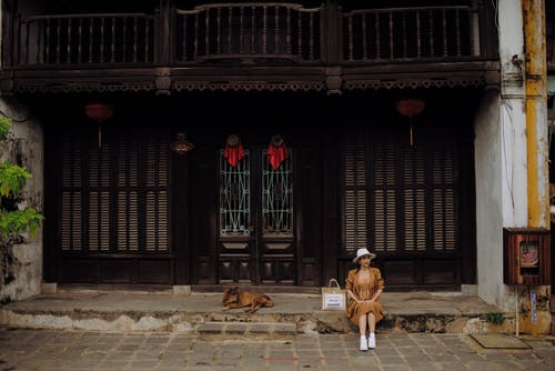 Smiling stylish female tourist in hat sitting against street dog and aged house facade during trip in city
