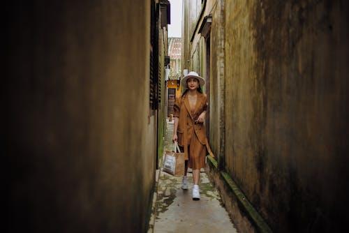 Trendy Asian tourist strolling on narrow street