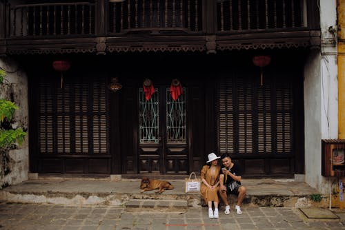 Asian couple sitting on house doorway and browsing smartphone