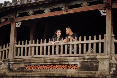 Happy young Asian couple leaning on wooden balcony railing while having pleasant conversation and looking at each other with smiles