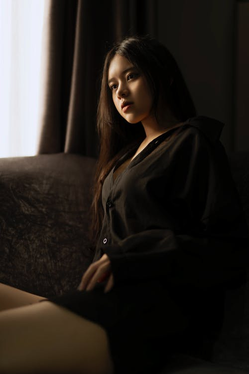 Gorgeous Asian woman resting on comfortable couch