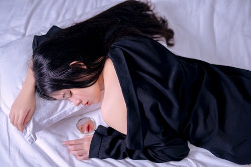 Top view of young gentle Asian female in black apparel with closed eyes lying on bed and reflecting in mirror