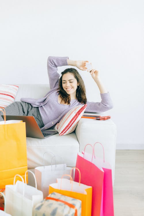 Woman in Gray Long Sleeve Shirt Sitting on White Couch