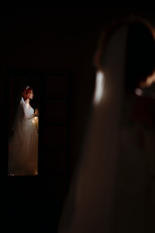 Side view of young ethnic woman in white dress with veil celebrating festive event at night