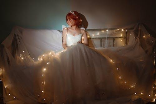 Asian bride among shiny garland at home