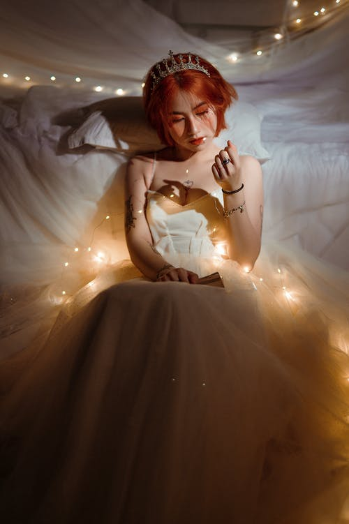 Young contemplative ethnic female in white dress with glowing garland looking down in bedroom at night