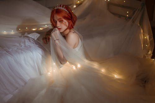 Charming Asian bride in white dress with glowing garland indoors