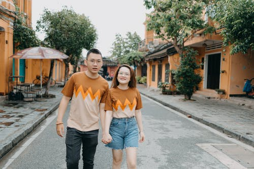 Cheerful ethnic couple in bright T shirts with patterns holding hands on contemporary street of city in daytime