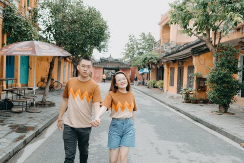 Cheerful young ethnic couple in eyeglasses promenading on urban street with green trees in daytime