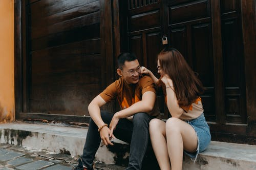 Happy young ethnic couple speaking and smiling while looking at each other on urban street near building