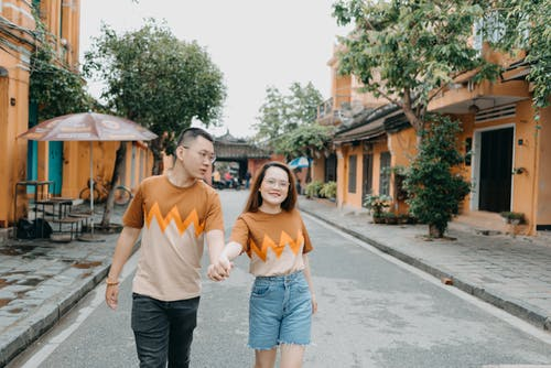 Cheerful ethnic couple strolling on urban street with small orange buildings and verdant trees in daytime