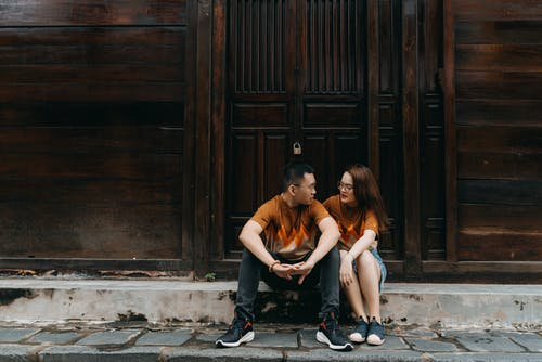 Young Asian couple talking on street with wooden building
