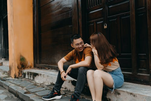 Happy ethnic couple talking while smiling and looking at each other on urban street with old buildings