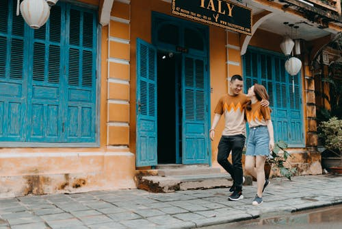 Full length of happy Asian couple in same t shirts hugging and looking at each other while walking on street near entrance of colorful building