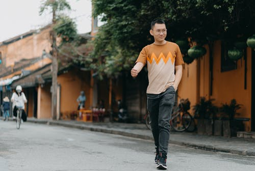 Full length of satisfied Asian male in casual clothes walking on city street while smiling and looking away