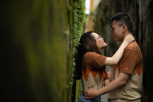 Loving couple embracing near wall with moss