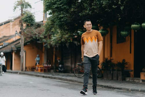 Full body of confident Asian man in casual wear walking on street at daytime while looking away and smiling