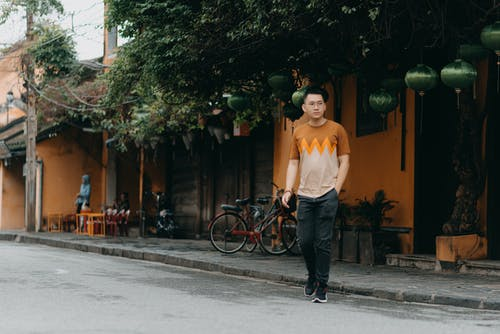 Full body of concentrated Asian man in casual outfit and glasses walking on city street near restaurant with Chinese lanterns and looking away at daytime