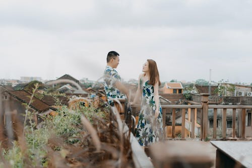 Side view of positive Asian couple in same summer wear and eyeglasses having date on rooftop terrace in gloomy day and looking at each other