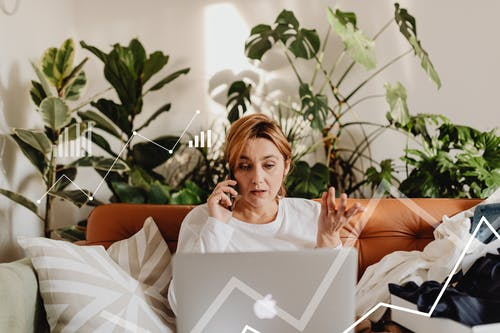 Woman in White Long Sleeves Using the Phone While Looking at the Laptop