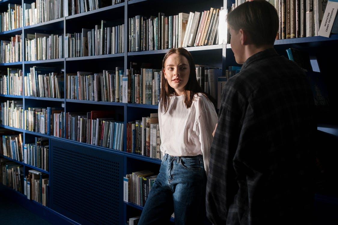 Man in White Dress Shirt Standing Beside Blue Wooden Book Shelf